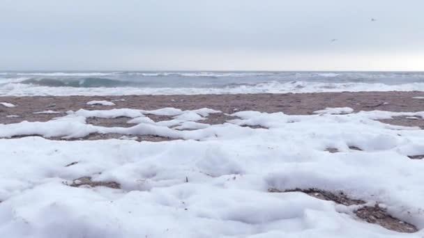 Sníh a mořské vlny na pláži. Akce v pomalém pohybu