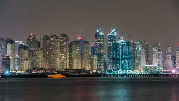 Dubai Marina skyline night timelapse as seen from Palm Jumeirah in Dubai, UAE.