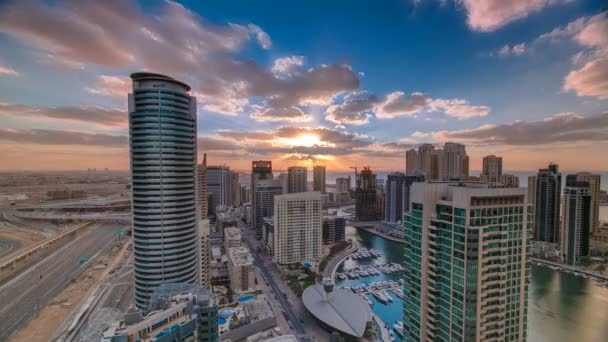 Modern skyscrapers and water channel with boats of Dubai Marina at sunset timelapse, United Arab Emirates.