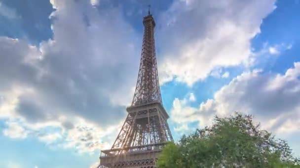 The Eiffel tower with warm rays of light in clouds during sunset timelapse hyperlapse.