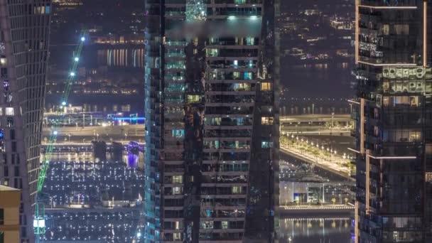 Canal in Dubai Marina with luxury skyscrapers around night timelapse, United Arab Emirates