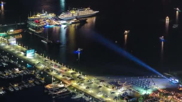 Přístav s yahcts a auta na parkoviště na noc zavřít pohled z mrakodrapu Dubai marina timelapse poblíž Palm Jumeirah