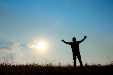 Silhouette of man worship with hands raised to the sky in nature