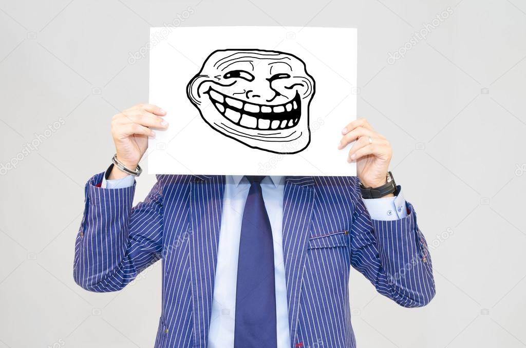 Business man hoding card with troll face on grey background