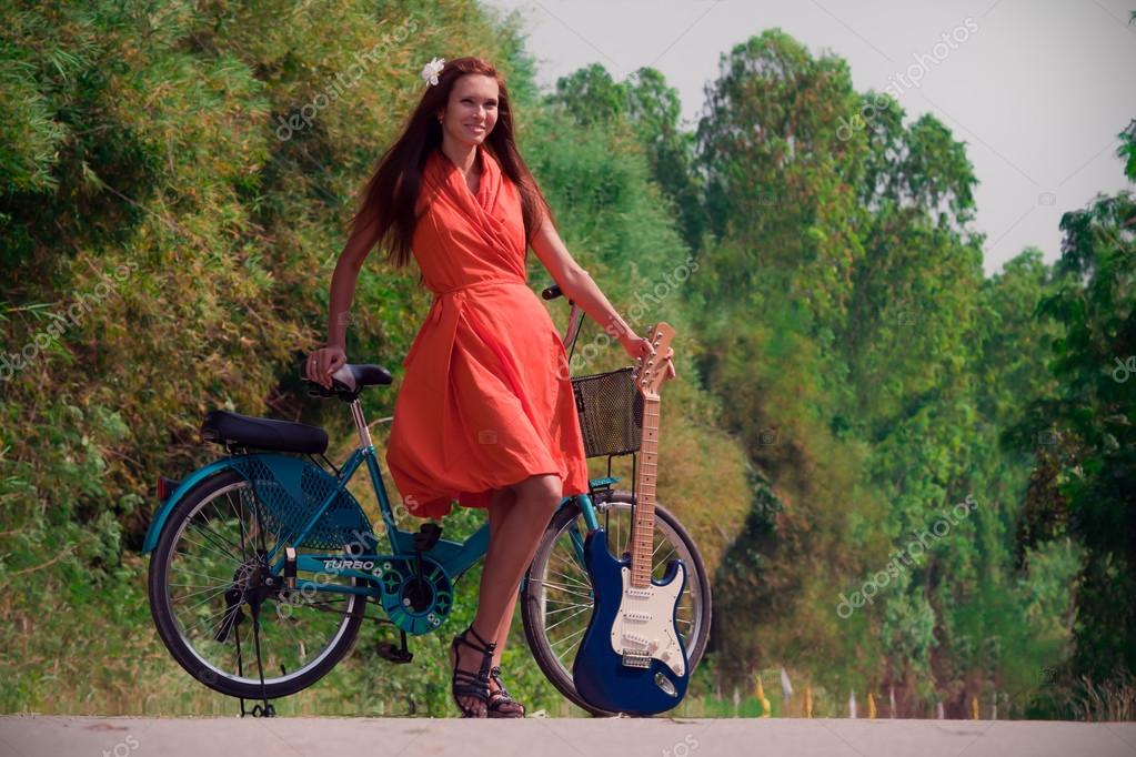 Girl on a bicycle with the guitar