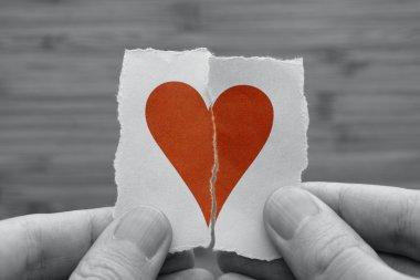 Man holds red broken paper heart in his hands