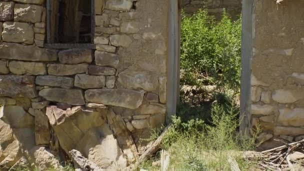An abandoned stone building with an empty doorway and window. A ghost town. The concept of the end of civilization.