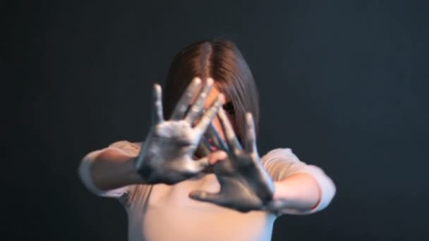 Modní dívka ve studiu rukama stříbrný