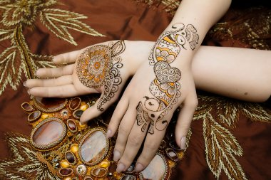 Two womans hands mehendi picture orange bright fabric with pleats