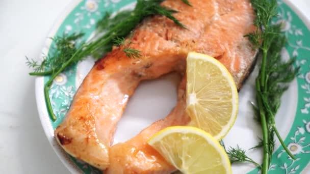 Vařím video. Šťavnaté a chutné červené ryby leží na slavnostním bílém talíři. Zelený kopr, petržel. Hladký pohyb kamery kolem talíře. Video dobré pro restaurace, kavárna menu, donáška čerstvých potravin