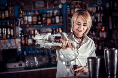 Charming woman bartending formulates a cocktail while standing near the bar counter in pub