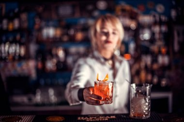 Girl barman makes a cocktail on the public house