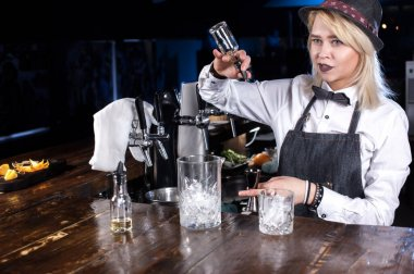 Focused woman bartender formulates a cocktail on the bar