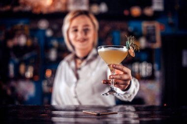 Girl barman formulates a cocktail in the bar