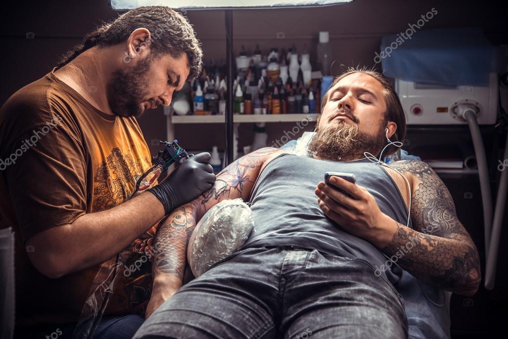 e94338408 Professional tattoo artist makes cool tattoo in tattoo parlor — Stock Photo