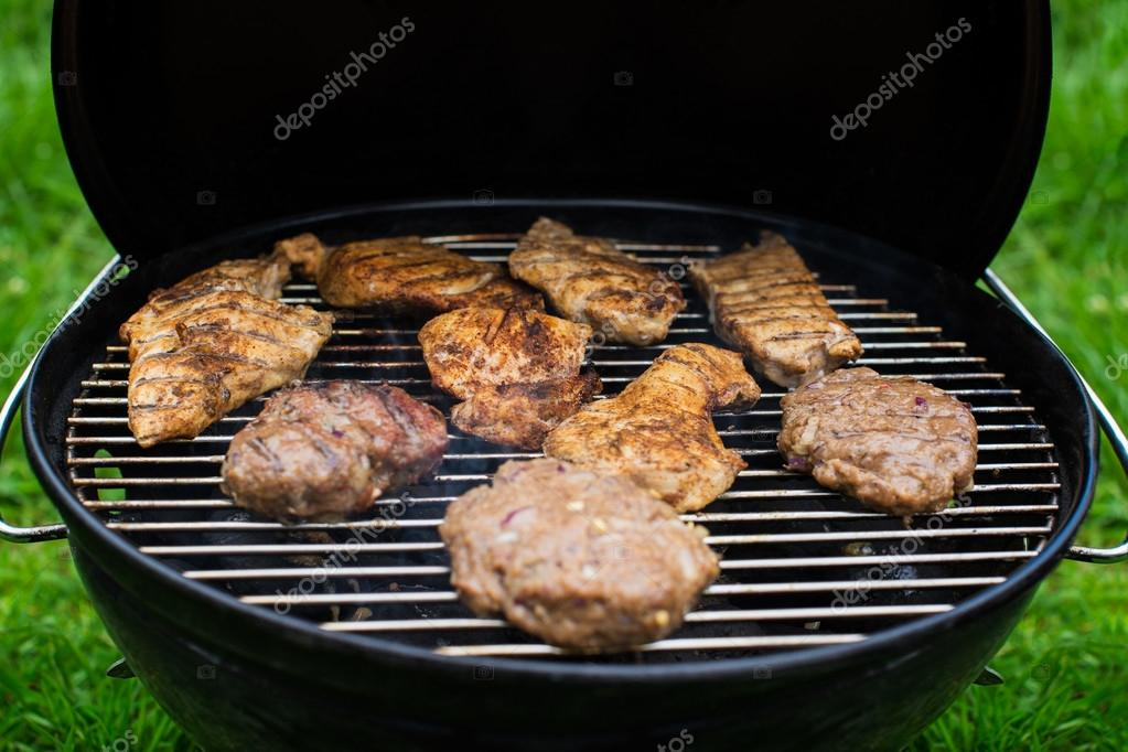 High angle view of succulent steaks and burgers cooking on a barbecue over the hot coals on a green lawn outdoors