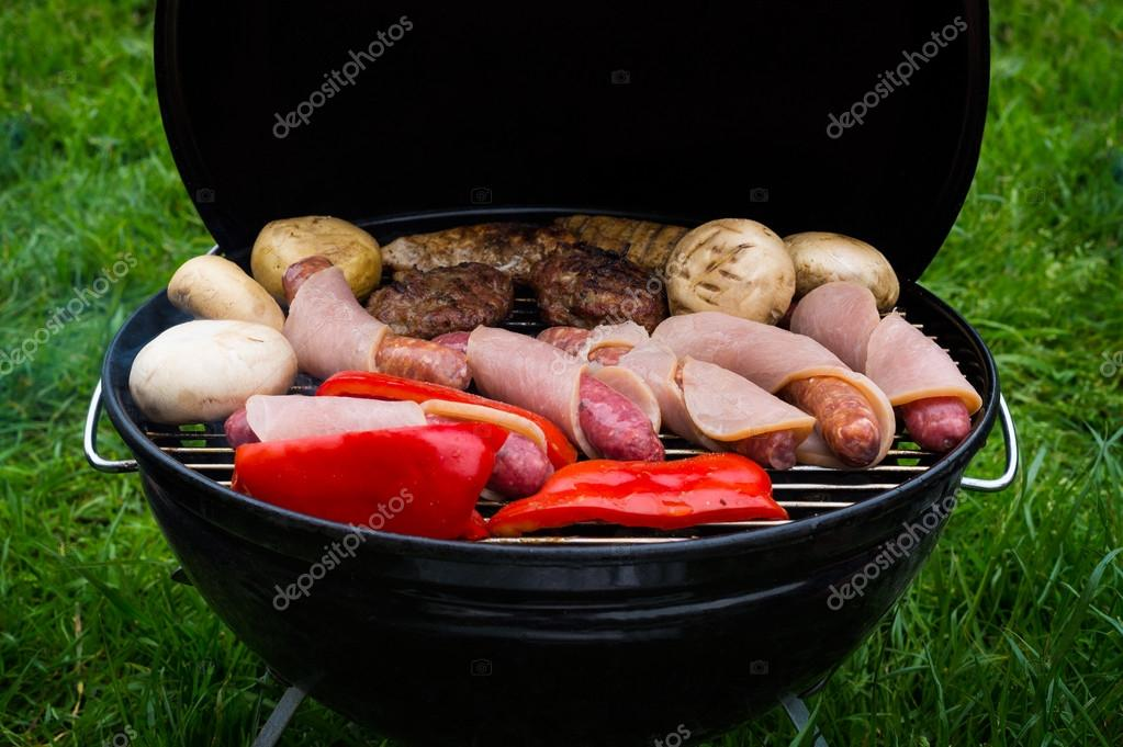High angle view of succulent steaks,burgers, sausages and vegetables cooking on a barbecue over the hot coals on a green lawn outdoors