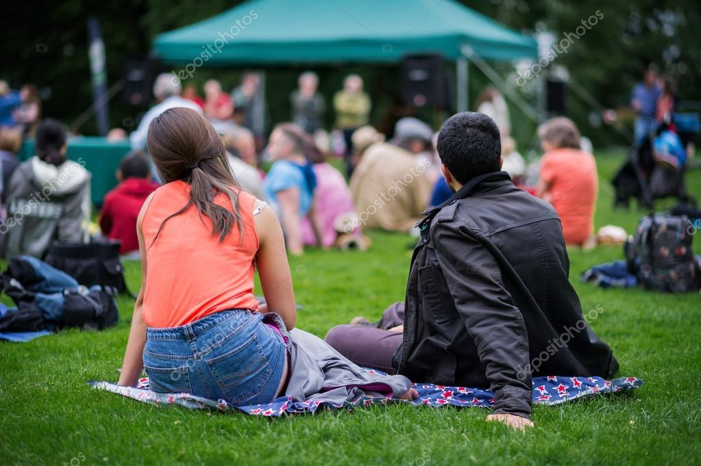 Friends sitting on the grass, enjoying an outdoors music, cultur