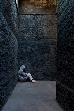 Scared, insane woman hiding in a corner of an ancient building.