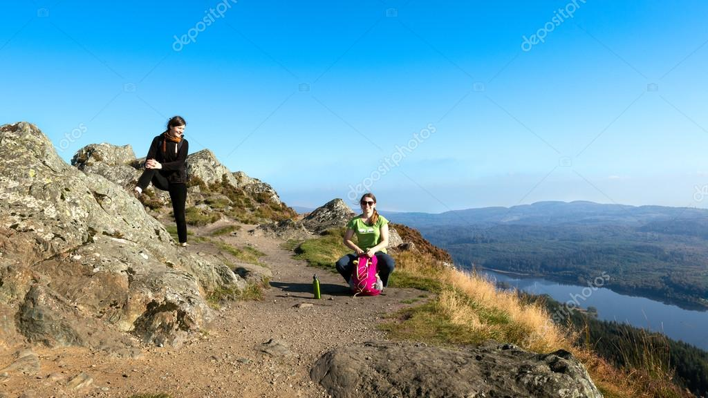 Two female hikers on top of the mountain taking a break and enjoying a valley view, Ben A'an, Loch Katrine, Highlands, Scotland, UK