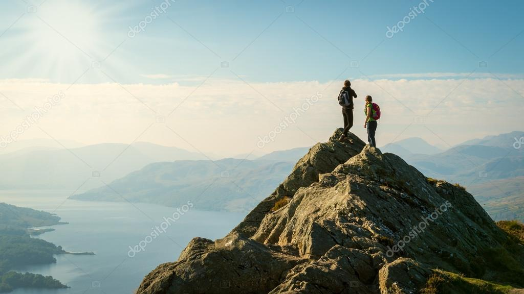 Two female hikers on top of the mountain enjoying valley view, Ben A'an, Loch Katrine, Highlands, Scotland, UK