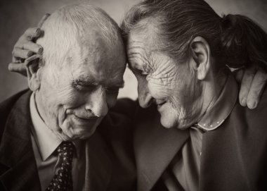 Cute 80 plus year old married couple posing for a portrait in their house. Love forever concept.