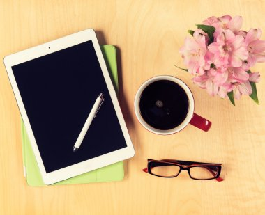 Office table with digital tablet, reading glasses and cup of coffee. View from above with copy space