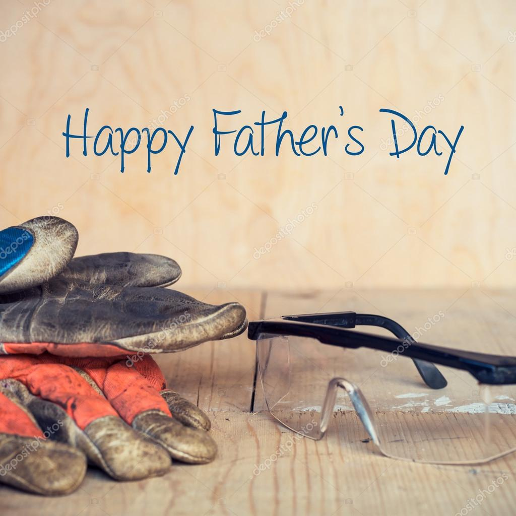 Fathers day concept, Old used safety glasses and gloves on wooden background