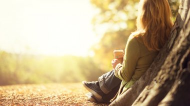 Autumn concept, anonymous woman enjoying takeaway coffee cup on sunny cold fall day