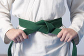 Photo Hands tightening green belt on a teenage dressed in kimono