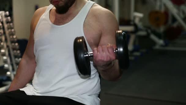 starker Mann, Bodybuilder, der in einem Fitnessstudio mit Hanteln trainiert. Zeitlupe