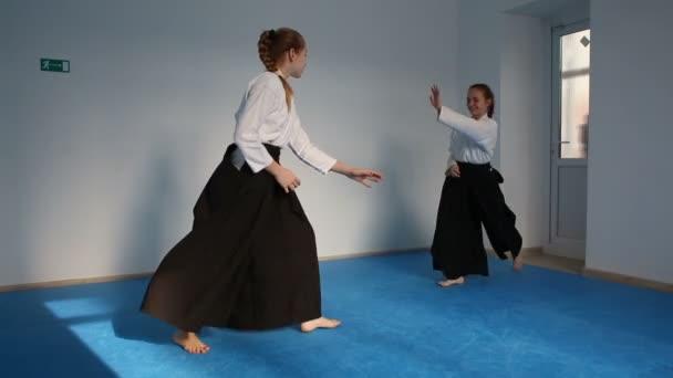 Két fekete hakamás lány gyakorolja az Aikidót.