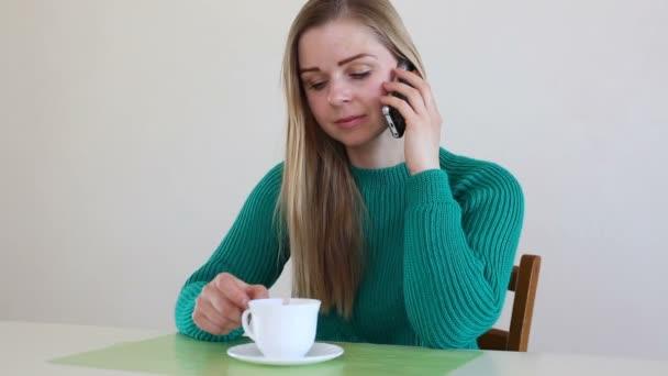 Krásná blondýnka pití kávy a mluví po telefonu
