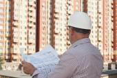 Photo An engineer examining blueprints