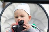 Photo A funny little baby boy  in a in a baby carriage
