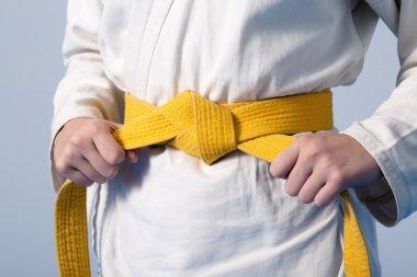 Hands tightening yellow belt on a teenage dressed in kimono