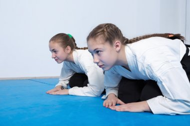 Two girls in hakama bow on Aikido training