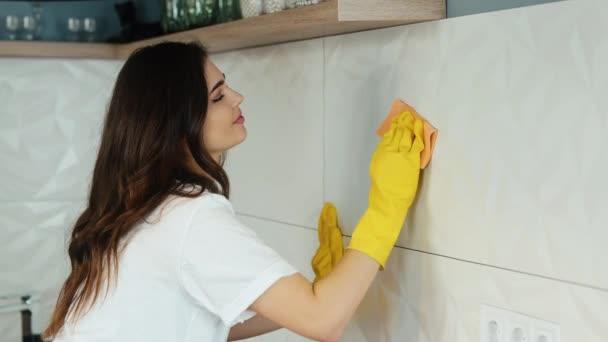 Mladá žena uklízí doma. Modelka brunetky čistí dlaždice na bílých stěnách v kuchyni. Ta holka uklízí špínu v bytě. zpomalený záznam.