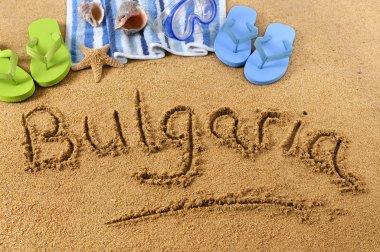 The word Bulgaria written on a sandy beach, with beach towel, starfish and flip flops. stock vector