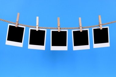 Several blank instant camera photo prints hanging on a rope or washing line isolated against a blue background.  Space for copy. stock vector