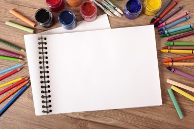 Blank white folded art book on a school desk with various paints, crayons and pencils. stock vector