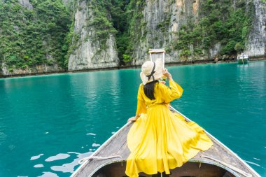 Beautiful woman in bright yellow dress, wearing cute hat, sitting on local long tail boat, watching the beauty of Ko Phi Phi Leh sea, Krabi, southern Thailand.