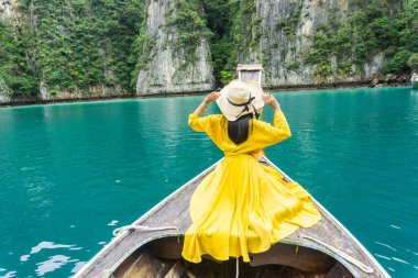 Beautiful woman in bright yellow dress, wearing hat with a black bow, on local long tail boat of Krabi, traveling to Phi Phi Island, Thailand.