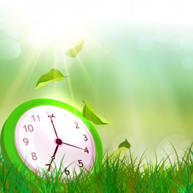 Time concept. Summer time. Alarm clock on the green grass