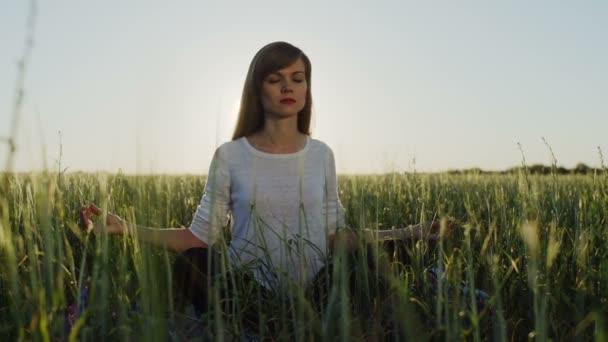 Žena sedí v lotosové pozici zen ukázal při západu slunce