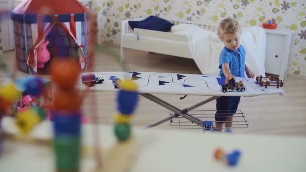 Kudrnatý dítě hraje s autíčko