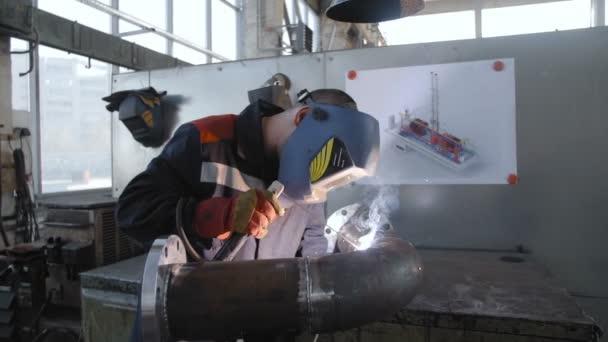 Dělník, svařování potrubí v dílně