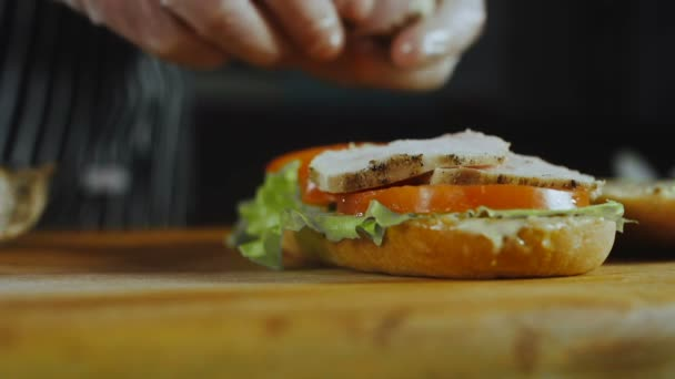 The Chef Hands Puts Chiken Slices On A Sandwich