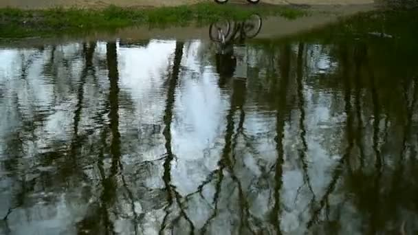 The Silhouette Of Biker Is Reflected In Water