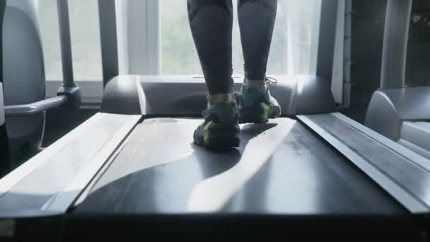 Nahaufnahme von Frauenfüßen in Turnschuhen geht auf Laufband